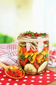 Vegetable salad in glass jar on wooden table, on bright background