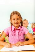 Girl sitting at desk in classroom and writing
