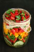 Vegetable salad in glass jar, on wooden background