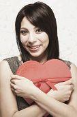 Hispanic woman hugging heart-shaped box