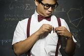 Nerdy Asian male student adjusting pencils in pocket