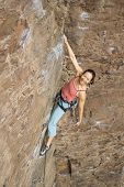 Asian woman rock climbing