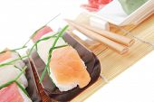 Japanese traditional cuisine - Set of Tuna (maguro) Salmon (sake) and Eel (unagi) Nigiri Sushi  with Wasabi  and Ginger on bamboo mat isolated over white background
