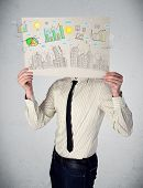 Businessman holding a paper in front of his head with charts and cityscape drawing
