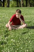 stock photo of depressed teen  - Depressed young Caucasian teen sitting on grass - JPG
