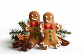 Smiling gingerbread men on white wooden background