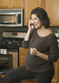 Pregnant Hispanic woman talking on telephone