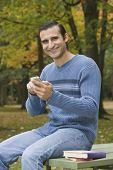 Hispanic man dialing cell phone