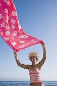 Mixed Race woman holding sarong in wind