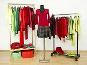 Wardrobe with complementary colors red and green clothes on hangers.