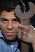 Hispanic man holding large wrench
