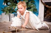 Little girl in a celebratory dress plays near the Christmas tree
