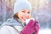 Beautiful Happy Smiling Winter Woman with Mug Outdoor. Laughing Girl Outdoors with Hot Drink