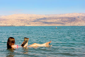 stock photo of israel people  - young woman reads a book floating in the waters of the Dead Sea in Israel - JPG