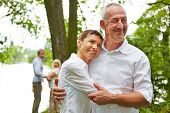 Senior couple in love embracing in nature in summer