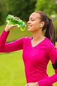fitness, park, drink and sport concept - smiling african american woman with player and earphones drinking from bottle outdoors