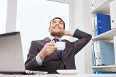 business, people, technology and work concept - smiling businessman sitting in front of laptop and typing in office