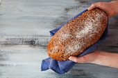 Loaf of freshly bread in female hands with napkin on color wooden table background