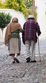 Old couple walking side by side