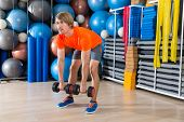 dumbbell deadlift blond man at gym weightlifting with swiss ball background