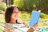 Happy Young Woman Reading Book In Hammock