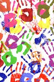 stock photo of messy  - Messy or untidy pattern of child handprints made from vivid acrylic paint isolated on a white paper background - JPG