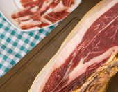 Top view of Serrano ham and plate, green tablecloth,
