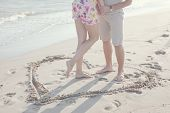 A Heart Shape Drawn In The Sand. Couple Standing Inside Heart Picture On The Sand. Summertime Fun