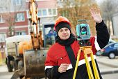 surveyor worker working with theodolite transit equipment at road construction site outdoors
