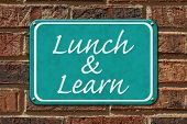 stock photo of lunch  - Lunch and Learn Sign A teal sign with the word Lunch and Learn on a brick wall - JPG