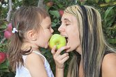 A mother playing with her daughter on apple tree