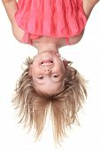 Little beautiful girl in pink clothes upside down isolated on wh
