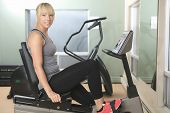 A woman cycling on exercise bike in gym