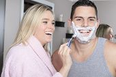 A woman to shave is boyfriend in bathroom
