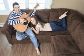 A Handsome man serenading his girlfriend with guitar at home in