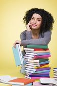 Smiling joyful student girl having a break while learning surrounded by multicolored books, isolated on yellow background.