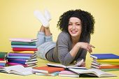 Happy smiling student girl lying down on the floor while learning surrounded by colorful books, isolated on yellow background.