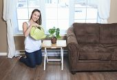 A Woman Watering The Plants in the living room