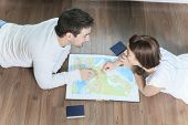 A Cheerful couple looking at a MAP in the living room