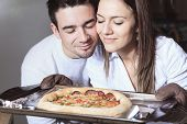 A Happy young couple eating pizza at the kitchen
