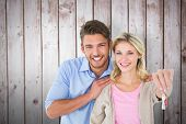 Attractive young couple showing new house key against wooden planks