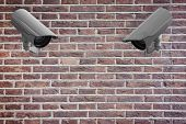 CCTV camera against red brick wall