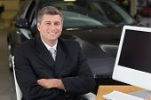 Smiling businessman sitting at his desk with arms crossed at new car showroom