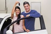 Smiling couple holding their new car key at new car showroom