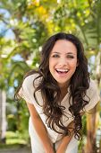 Pretty brunette smiling at camera on a sunny day