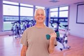 Senior man lifting hand weights against spinning exercise bikes in gym room