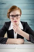 Thinking redhead businesswoman against wooden planks