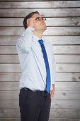 Thinking businessman tilting glasses against wooden planks