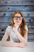 Pretty redhead thinking and looking up against wooden background in blue