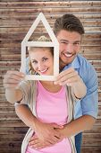 Young couple hugging and holding house outline against wooden planks